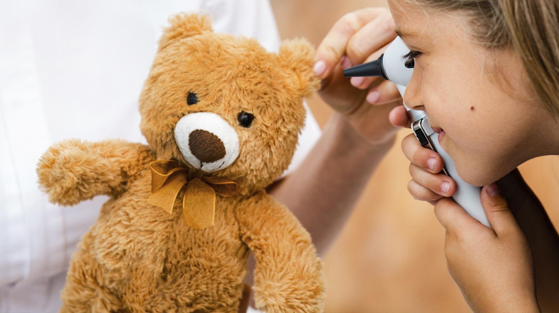Mittelohrentzündung: Kind schaut einem Teddy mit einem Otoskop ins Ohr.